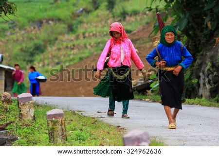 "HAGIANG, VIETNAM - SEPTEMBER 19 : Unidentified  women hill tribes of Vietnam carry and walking on the road Sep. 2015, 19 in Hagiang, Vietnam. ""Hmong"" is hill tribes that live on the high mountain."