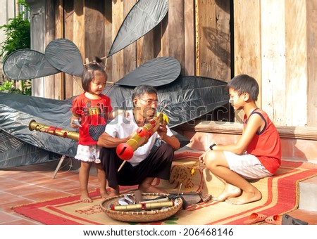 HAI DUONG, VIETNAM, July 14, 2014 he and his granddaughter (name unknown) in rural Hai Duong, flute kites are made - stock photo