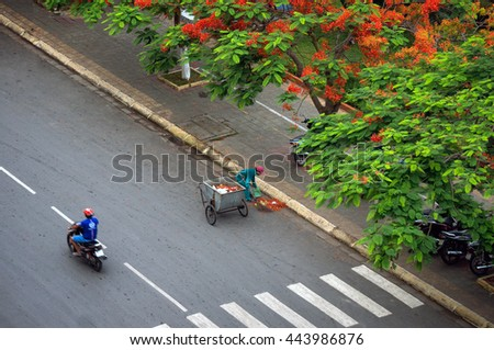 HAI PHONG, VIETNAM, June 19, 2016 the woman, silent, working as street sweeping Hai Phong, Vietnam, in the summer