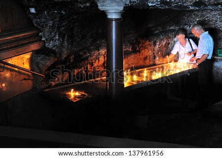 """HAIFA, ISR - JULY 07:Visitors at Stella Maris Carmelite Monastery on July 07 2010.The cave situated below the altar called """"Elijah's Cave"""" where the Old Testament prophet is believed to have lived. - stock photo"""