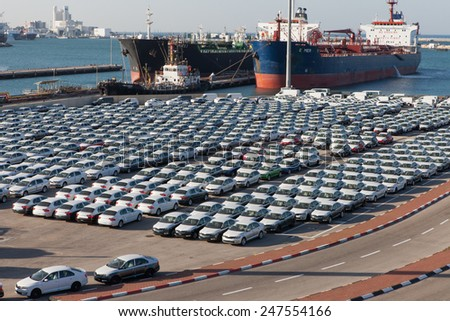 Haifa, Israel - January 23, 2015: Rows of new cars covered in protective white sheet parked in Haifa's port platform - stock photo