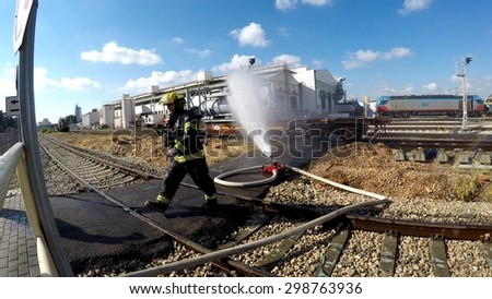 HAIFA, ISRAEL - JUNE 30, 2015: Firefighters from Northern Israel with protective gear during simulation drill of leak of Bromine chemical in a container car of train. Water stream is applied.
