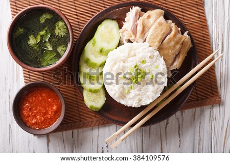 Hainanese chicken rice with cucumber closeup on a plate and broth. Horizontal top view - stock photo