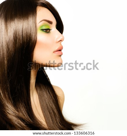Hair. Beautiful Brunette Girl. Healthy Long Brown Hair. Beauty Model Woman with Green makeup. Trendy Spring Make-up - stock photo