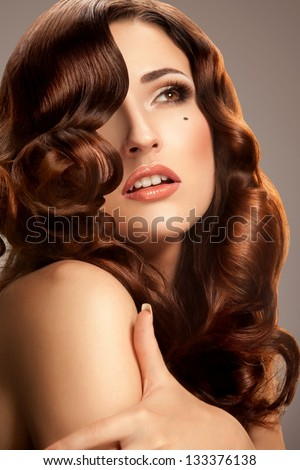 Hair.Beautiful Woman with Curly Long Hair. Red Lips.