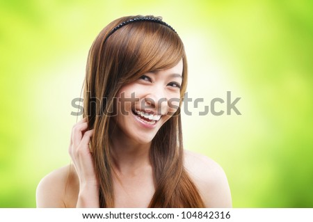 Hair care. Cheerful Asian female combing her hair using finger - stock photo