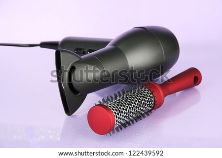 hair dryer and comb brush, on purple background - stock photo