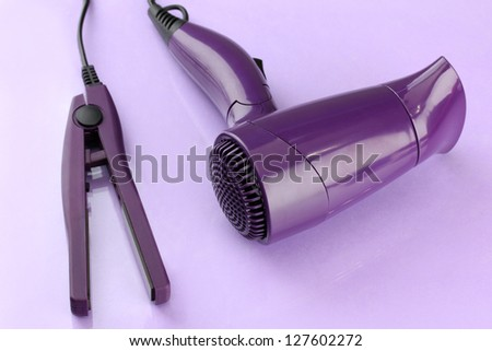 Hair dryer and straighteners  on purple background - stock photo