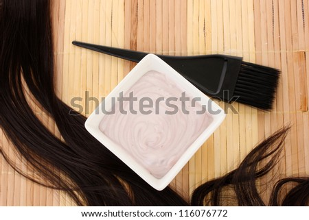 hair dye in bowl and brush for hair coloring on beige bamboo mat, close-up - stock photo
