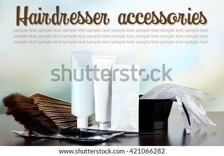 Hair dye kit and hair samples of different colors, on wooden table, on light background - stock photo