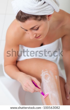 Hair removal - young woman is shaving her leg