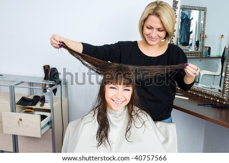 hair stylist and woman in salon having fun - stock photo