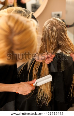 Hair stylist at work - hairdresser combing hair to the customer before doing hairstyle in a professional salon - stock photo