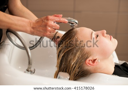 Hair stylist at work - hairdresser washing hair to the customer before doing hairstyle - stock photo