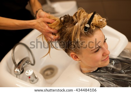 Hair stylist at work - hairdresser washing hair to the customer before doing hairstyle