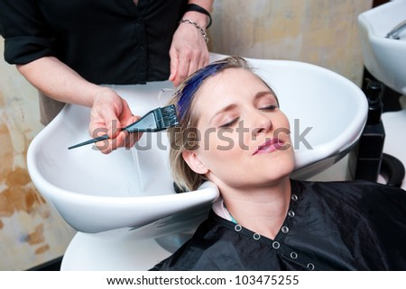 hair stylist coloring woman hair at salon