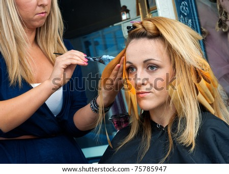 hair stylist coloring woman hair in salon - stock photo
