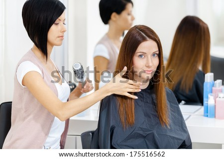 Hair stylist does hair style of woman in hairdressing salon. Concept of fashion and beauty - stock photo