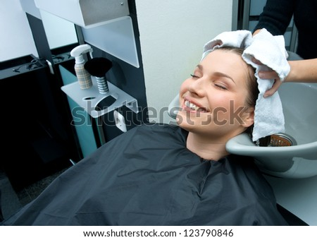 hair stylist drying woman hair with towel in salon
