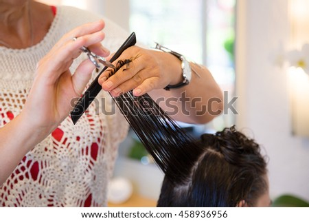 Hair stylist is cutting hair of a young female