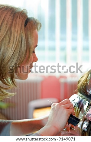 Hair stylist painting hair. Aluminum foils help to bleach separate mops of hair - stock photo