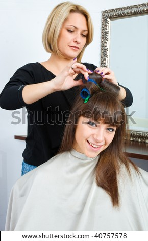 hair stylist putting rollers in woman hair - stock photo