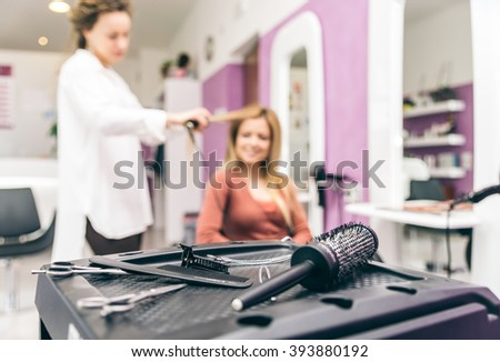 Hair stylist straightening hair to her customer in a modern hairdresser salon, closeup on brushes and scissors - stock photo