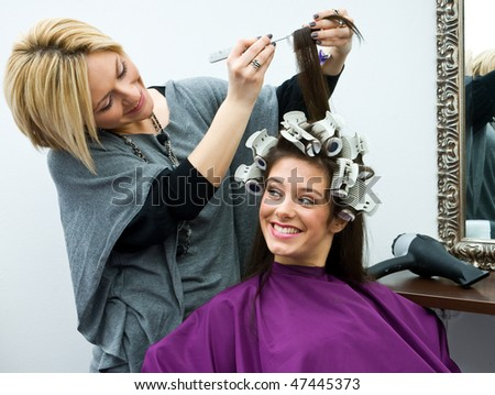 hair stylist work on woman hair and having fun - stock photo