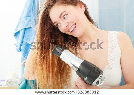 Haircare. Beautiful long haired woman drying hair in bathroom - stock photo