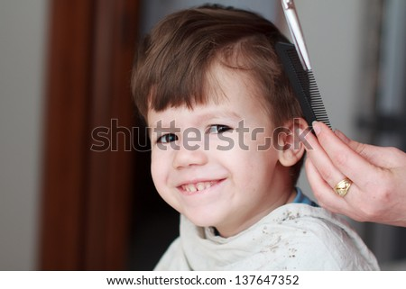 Haircut for little boy, professional barber, teeth smile - stock photo