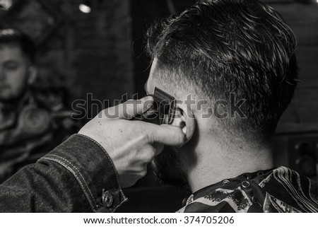 Haircut men Barbershop. Men's Hairdressers; barbers. Barber cuts the client machine for haircuts. - stock photo