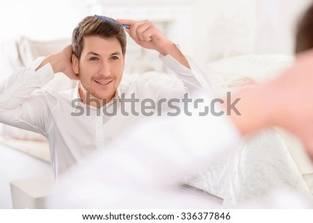Hairdo time. Appealing young guy smiles gently while combing his hair in front of the mirror.  - stock photo