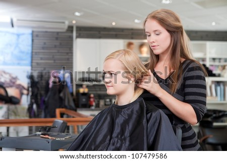Hairdresser and client in beauty salon.