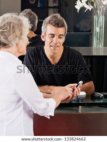 Hairdresser and female client discussing over mobilephone at salon counter - stock photo