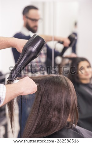 Hairdresser blow dry beautiful  woman hair in hairdressing salon.