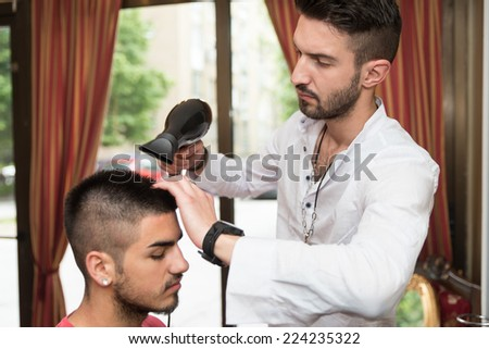 Hairdresser Blow Dry Man's Hair In Shop - Handsome Man At The Hairdresser Blow Drying His Hair - stock photo
