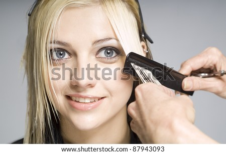 Hairdresser cutting client or customer with comb - stock photo
