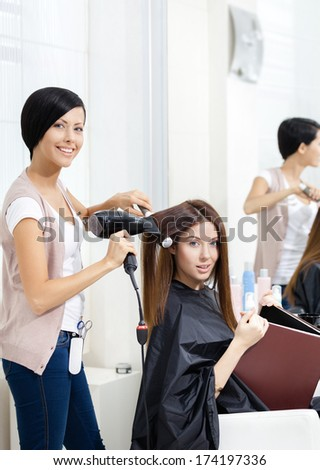 Hairdresser does hair style of woman in hairdressing salon. Concept of fashion and beauty - stock photo
