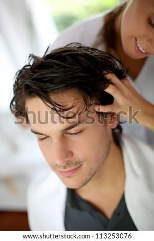 Hairdresser doing hair massage to customer - stock photo