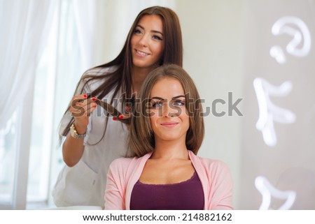 Hairdresser doing haircut for women in hairdressing salon. Concept of fashion and beauty. Positive emotion - stock photo