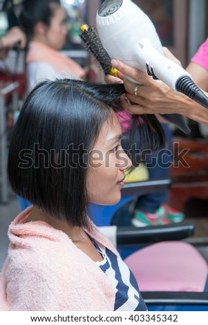 hairdresser dries the hair customers with hairdryer - stock photo