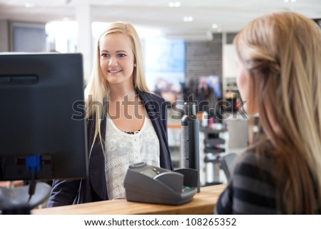 Hairdresser helping client at beauty salon. - stock photo