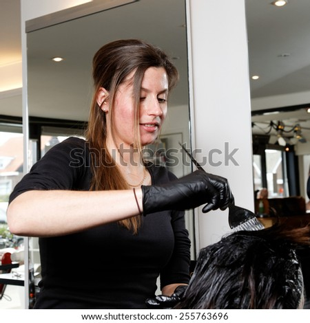 hairdresser in a salon colors the hair of a customer  - stock photo