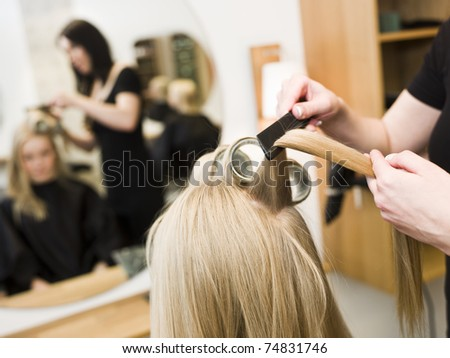Hairdresser in action with blond customer close up