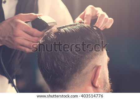 Hairdresser makes hairstyle a man with a beard  - stock photo