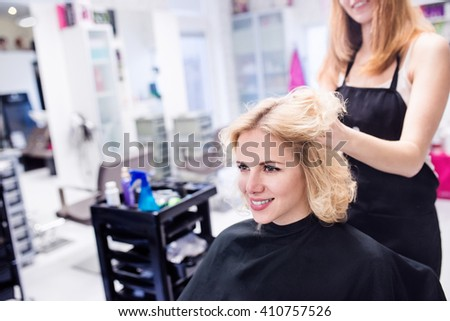 Hairdresser making a new haircut to her handsome client - stock photo