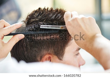 Hairdresser making haircut to young man at beauty parlour - stock photo