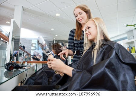 Hairdresser pointing at magazine held by female customer in parlor