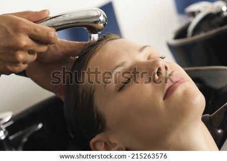 Hairdresser rinsing woman's hair in salon, customer with eyes closed, close-up - stock photo