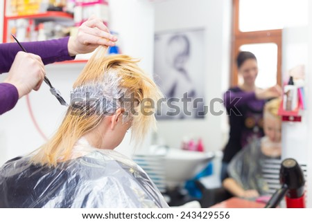 Hairdresser salon. Hair colouring in process. Beautiful young woman dyeing hairs.